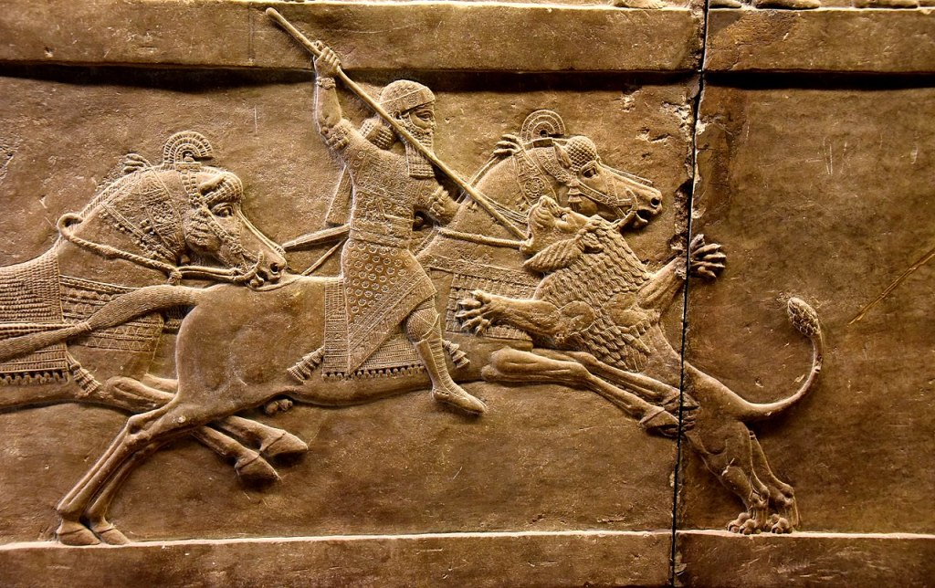 Ashurbanipal on his horse thrusting a spear at a lion's head.