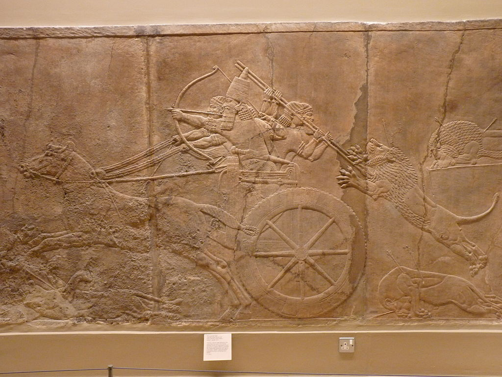 The king shoots arrows from his chariot, while huntsmen fend off a lion behind.